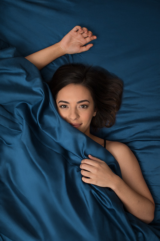 Model on bed with blue sheets_Vertical